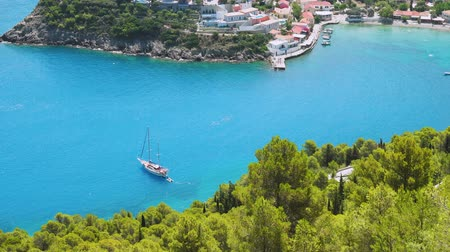 Luxury Sailing yacht in the blue bay. Vacations in mediterenean sea. Colorful harbor, remote nature of Assos village, secluded Islands in Greece. Travel adventure carefree and happiness concept.