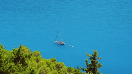 elvonult : Luxury white sailing yacht in the open blue bay. Vacations in mediterenean sea. Secluded Islands in Greece. Travel adventure carefree and happiness concept. Stock mozgókép