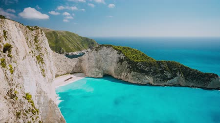 navagio : Timelapse of the world famous Navagio beach, Zakynthos, Greece. Turquoise sea water rolled to white sand beach with Shipwreck. Clouds moving in sky. Fist tourist boat arrived the bay