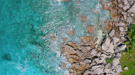 4k aerial view vertical video waves arriving on rocky granite rocks of La Digue island. Crystal clear water with great visibility Stock Footage