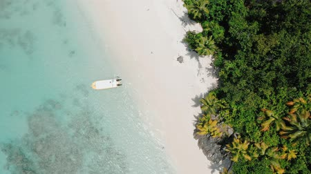 mahe : Aerial drone 4k bird eye footage with circle movement of tropical paradise beach with coconut trees and lonely tourist boat in turquoise lagoon water Stock Footage