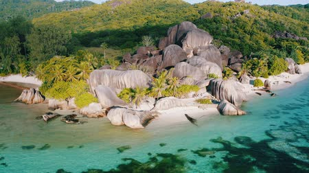 Aerial drone 4k footage of the well known beautiful Anse Source Dargent beach on La Digue island, Seychelles. Warm sunset light