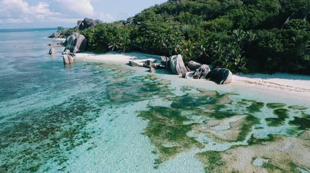 most : Aerial drone 4k side flight above Anse Source Dargent beach on La Digue island, Seychelles. Morning sun light, clear shallow lagoon and picturesque granite rocks