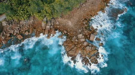 Overhead aerial drone 4k flight over granite boulders near to Anse Bazarca beach. Ocean waves breaking on rocks. Mahe island, Seychelles