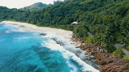 mahe : Epic aerial drone 4k flight towards tropical paradise Anse Bazarca beach on Mahe island. White sand, crystal clear turquoise ocean waves breaking on reef. Magical jungle at the background. Seychelles