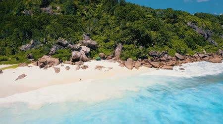 Petite Anse, La Digue, Seychelles. 4K drone circle flight over turquoise crystal clear ocean water near to tropical paradise beach with white sand beach Stock Footage