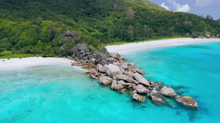 Grand Anse and Petite Anse beaches La Digue Island, Seychelles. Aerial drone circle flight over turquoise crystal clear ocean water and huge rocks formation Stock Footage