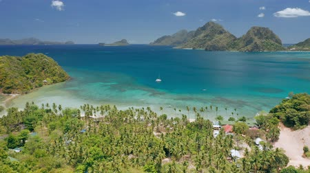 Aerial drone panoramic coastline view of Las Cabanas beach with sail boat in blue water, sandy beach and palm trees. El Nido, Palawan, Philippines. Summer and travel vacation concept