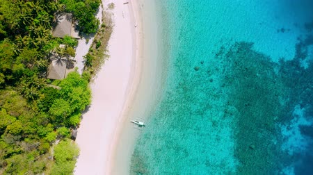 Aerial footage of tropical beach on Helicopter island with palm trees, blue lagoon, azure clear water and coral reef. Lonely tourist boat at white sandy beach. El Nido, Palawan Philippines