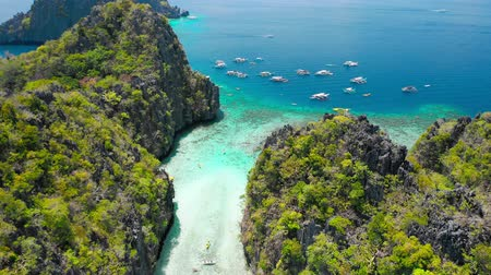 архипелаг : Big Lagoon, El Nido, Palawan, Philippines. Drone aerial fly between limestone cliffs above shallow water of entrance. Torist banca boat of Island Hopping Tour A wait outside