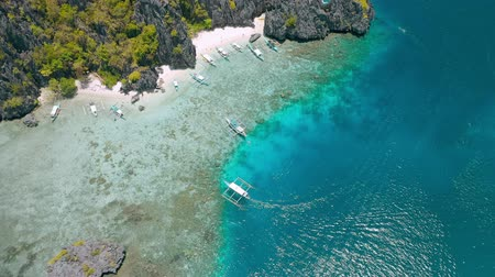 Tourist tour trip banca boats in shallow water at Shimizu Island in El Nido, Palawan, Philippines. Intact coral reef abound the island Stock Footage