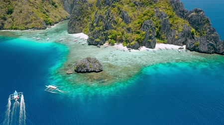 Aerial drone footage of tourist banca boat approaching Shimizu Island beach in El Nido, Palawan, Philippines. Rocks and crystal clear shallow turquoise lagoon water in front of the island Stock mozgókép