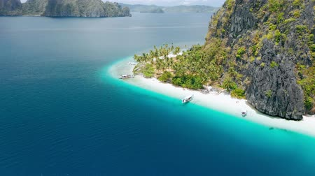 Aerial drone view of tropical Ipil beach, Pinagbuyutan Island, El Nido, Palawan, Philippines. Turquoise blue water, sandy beach and palm trees - vacation, travel tourism concept