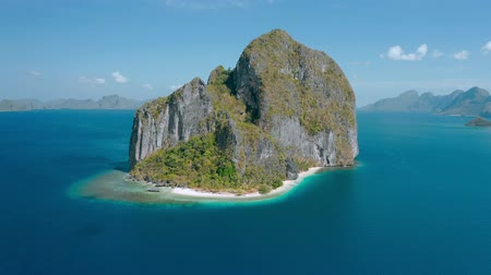 Aerial drone view of Karst limestone rocky Pinagbuyutan Island in blue sea of El Nido, Palawan, Philippines. Tropical Ipil palm beach located in front Stock mozgókép