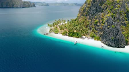 Aerial drone footage of tropical Ipil beach, Pinagbuyutan Island, El Nido, Palawan, Philippines. Turquoise water, sandy beach, palm trees and trip boats - vacation, travel tourism concept
