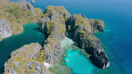 Aerial view of small and big lagoon on Miniloc Island. El-Nido, Palawan. Philippines. Limestone rock formation overgrown with plants and blue shallow bays in tour A