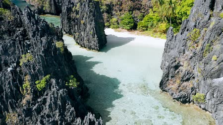 conhecido : Aerial drone view over clear shallow lagoon water surrounded by sharp rocky formations. Hidden Beach, El Nido Palawan National Park Philippines. Summer tourist destination