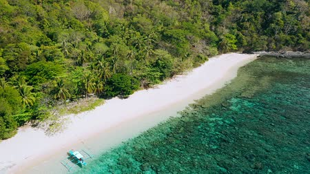 Remote white sand beach on Helicopter Island, Philippines. Aerial drone view of exotic island with lush foliage and beautiful coral reef. Tourist routes in the Philippines. Unique must see spot Stock mozgókép