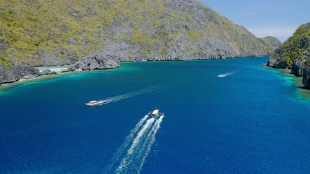 Drone follow Island hopping boats in strait between Matinloc and Tapiutan Island in El Nido, Palawan, Philippines