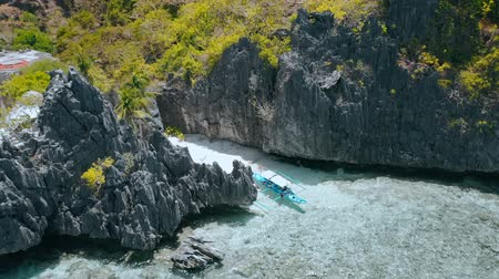 rezervasyon : Aerial circling movement around Matinloc Shrine. El Nido, Palawan, Philippines. Bizarre limestone rocks and lonely boat in shallow water with colorful coral reef. Tour C Stok Video