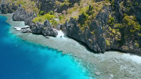 Aerial view of tourist boat moored at Matinloc Shrine. El Nido, Palawan, Philippines. Bizarre limestone mountain rocks and coral reef und crystal clear blue water. Sightseeing of Hopping island Tour C