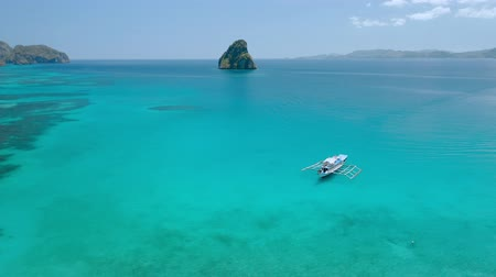 Aerial drone view of island hopping tourist boat swimming over shallow water in turquoise blue Cadlao lagoon. El-Nido. Palawan. Philippines