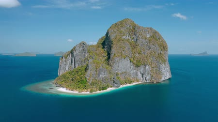 архипелаг : Aerial drone view of Karst rocky Pinagbuyutan Island in blue sea of El Nido, Palawan, Philippines. Amazing tropical nature landscape and travel concept. Стоковые видеозаписи