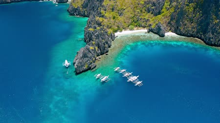 Aerial view of diving boats moored near secret lagoon on Miniloc Island. El-Nido, Palawan. Philippines. Bizarre limestone rock formation and blue lagoon with coral reef make this place unique Stock mozgókép