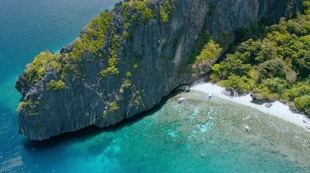 Aerial view above coral reef and tourist banca boats on Entalula beach, Bacuit Bay, El-Nido. Palawan Island, Philippines Stock Footage