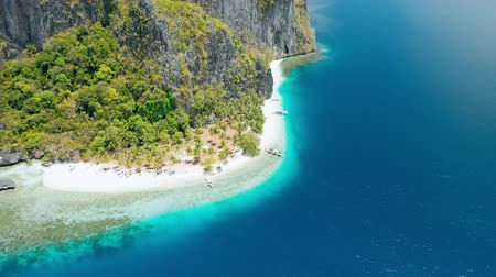 Breathtaking Pinagbuyutan Island. El Nido, Palawan, Philippines. Paradise tropical sandy Ipil Beach with azure turquoise sea water, coconut palm trees and local banca boats moored