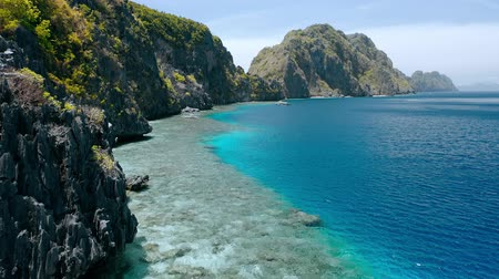 conhecido : Matinloc island, El Nido, Palawan, Philippines. Aerial view of picturesque sea coast, crystal clear water, sharp cliffs and coral reefs. Unique spot, top touristic destination and must-see place