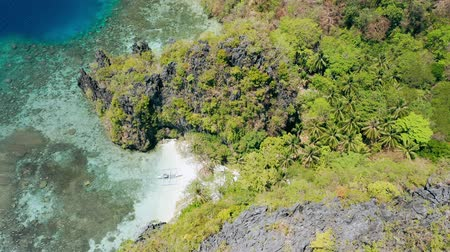 Aerial footage of small beach near big lagoon with lonely banca local boat on paradise sandy beach. Miniloc island El-Nido, Palawan. Philippines. Unique spot on tour A island hopping trip Stock mozgókép