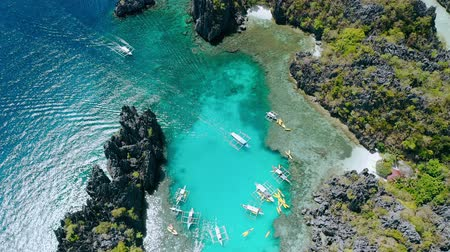 известное место : Aerial top down view of tourist boat arriving into the Small lagoon in El-Nido, tour A, Palawan