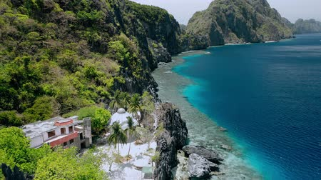 rezervasyon : Aerial fly over Matinloc Shrine along the coastline. El Nido, Palawan, Philippines. Bizarre limestone mountain rocks and coral reef und crystal clear blue water. Sightseeing of Hopping island Tour C