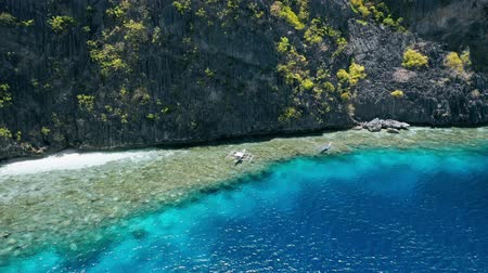 césar : Aerial circling footage of tourist boats hover over coral reef near Matinloc shrine. El Nido, Palawan Philippines