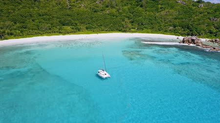 domingo : Aerial 4k drone footage of white yacht moored in remote lagoon with crystal clear turquoise water and rainforest in background. La Digue Island. Seychelles Stock Footage
