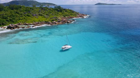 zondag : Aerial 4k drone footage of lonely white yacht moored in crystal clear turquoise lagoon water on tropical La Digue Island. Luxury summer vacation