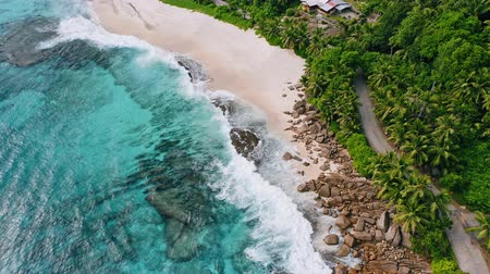 formasyonlar : Aerial view of waves breaking on the rocks and white beaches surrounded by coconut palm trees at Anse Bazarca, on Mahe Island, Seychelles Stok Video