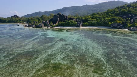 anse : Aerial footage circling around granite boulders on famous Anse Source dArgent tropical beach at sunny day light during low tide shallow lagoon. La Digue Island, Seychelles Stock Footage