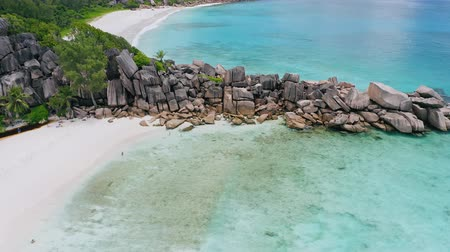 most : Aerial footage of unique huge granite boulders ridge made by nature and surrounded by paradise white sand beaches with crystal clear turquoise blue ocean water. La Digue island, Seychelles Dostupné videozáznamy
