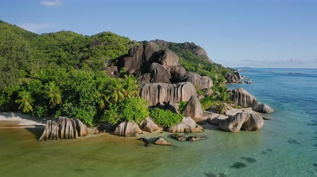 pristine : Aerial footage of famous granite boulders on Anse Source dArgent tropical beach at sunny day bright light with shallow lagoon in low tide. La Digue Island, Seychelles