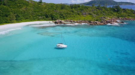 elvonult : Aerial view of lonely luxury catamaran yacht in blue lagoon. La Digue island, Seychelles Stock mozgókép