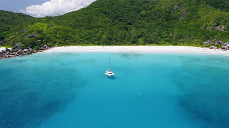 catamaran : Aerial view footage of luxury catamaran yacht moored in clear turquoise blue ocean water of Petite Anse sandy beach of La Digue island, Seychelles. Travel concept
