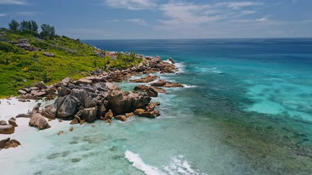 pristine : Aerial fly footage along tropical coastline with huge granite rocks and blue ocean waves on paradise beach Anse Coco. La Digue island, Seychelles