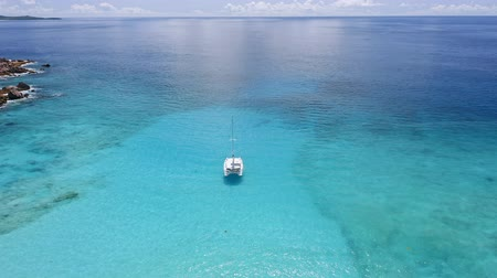 tükrözött : Aerial view of lonely luxury catamaran yacht in crystal clear blue lagoon with reflected light. La Digue island, Seychelles