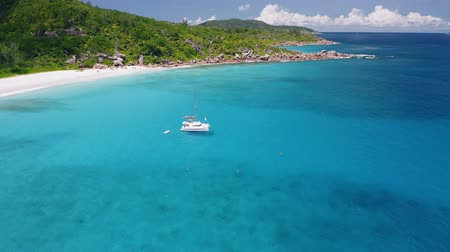 elvonult : Aerial view footage of lonely luxury catamaran yacht moored in crystal clear turquoise blue ocean water of Petite Anse sandy beach of La Digue island, Seychelles. Travel concept Stock mozgókép