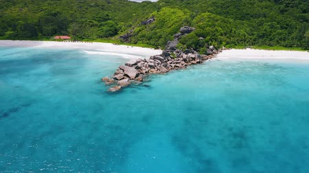 kotva : Aerial footage approaching unique granite boulders surrounded by crystal clear turquoise blue ocean water at Grand and Petite Anse beaches of La Digue island, Seychelles