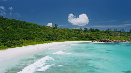 attitude : Aerial view of tropical paradise beach Anse Coco. Unrecognized lone tourist couple walk on white sand coast with blue blue lagoon and rolling waves. La Digue island, Seychelles
