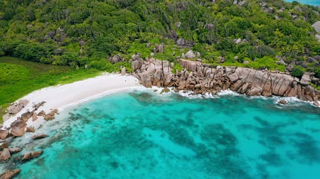 runaway : Aerial view of most beautiful tropical hidden beach with white sand and aquamarine bay water surrounded by bizarre unique granite boulders. La Digue island, Seychelles Stock Footage