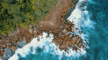 mahe : Aerial drone 4k stable footage over granite boulders near to Anse Bazarca beach. Ocean waves breaking on rocks. Mahe island, Seychelles